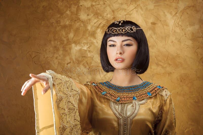 Όμορφη αιγυπτιακή γυναίκα όπως την Κλεοπάτρα που δείχνει το δάχτυλο μακριά στο χρυσό υπόβαθρο στοκ φωτογραφία με δικαίωμα ελεύθερης χρήσης