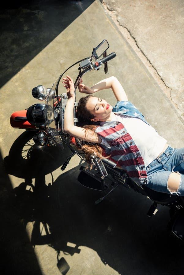 Όμορφη αισθησιακή νέα γυναίκα στη φανέλλα τζιν που βρίσκεται στη μοτοσικλέτα στοκ εικόνες