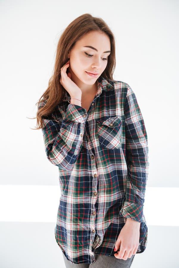 Όμορφη αισθησιακή νέα γυναίκα στο πουκάμισο καρό που στέκεται και που χαμογελά στοκ φωτογραφία με δικαίωμα ελεύθερης χρήσης
