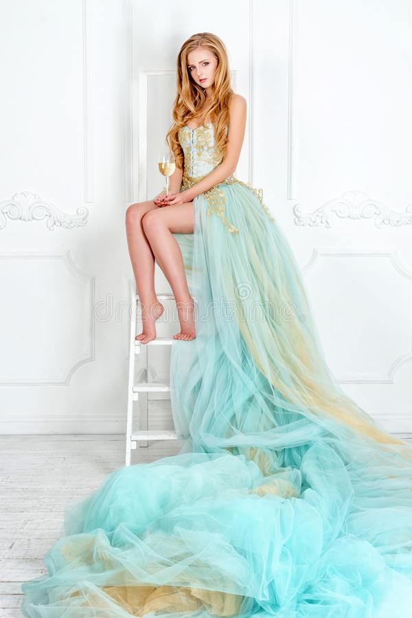 Όμορφη αισθησιακή ξανθή γυναίκα στο πανέμορφο μακρύ ποτήρι εκμετάλλευσης φορεμάτων του άσπρου κρασιού με το μπουκάλι που στέκεται στοκ εικόνες με δικαίωμα ελεύθερης χρήσης