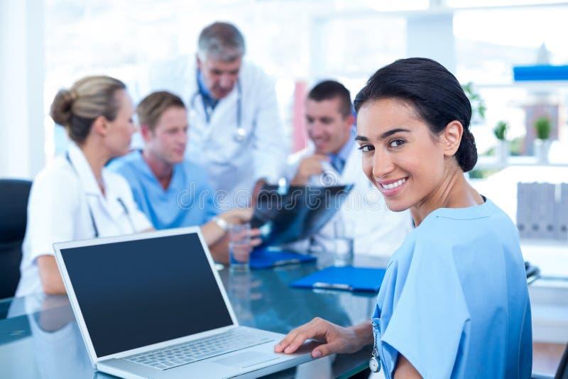 Όμορφη δακτυλογράφηση γιατρών χαμόγελου στο πληκτρολόγιο με την ομάδα της πίσω στοκ εικόνα με δικαίωμα ελεύθερης χρήσης