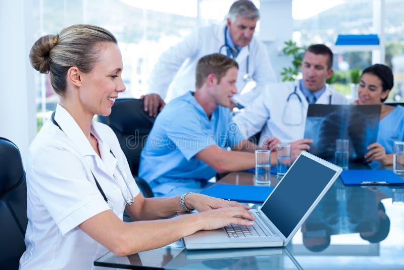 Όμορφη δακτυλογράφηση γιατρών χαμόγελου στο πληκτρολόγιο με την ομάδα της πίσω στοκ εικόνες