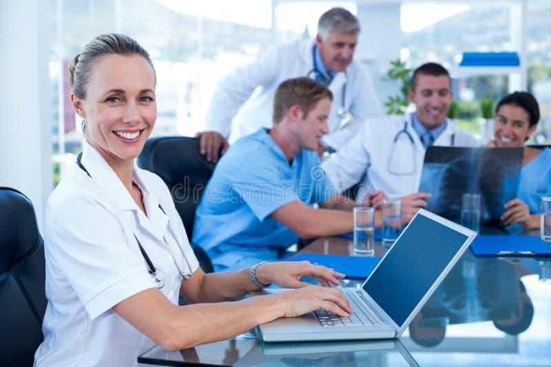 Όμορφη δακτυλογράφηση γιατρών χαμόγελου στο πληκτρολόγιο με την ομάδα της πίσω στοκ εικόνες με δικαίωμα ελεύθερης χρήσης