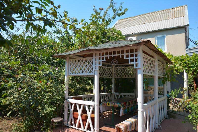 Όμορφη αλκόβα, ξύλινος άξονας, περίπτερο, κιόσκι, θερινό σπίτι, σπίτι κήπων στον κήπο στοκ φωτογραφία