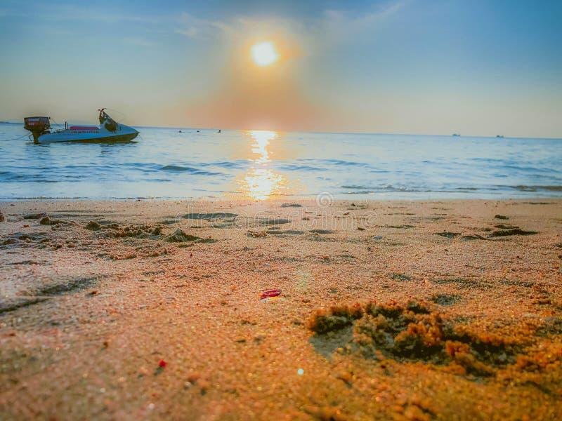 Όμορφη αμμώδης παραλία με ηλιοβασίλεμα με πολύχρωμο ουρανό και δραματικά σύννεφα πάνω από κυματιστή θάλασσα στοκ φωτογραφίες