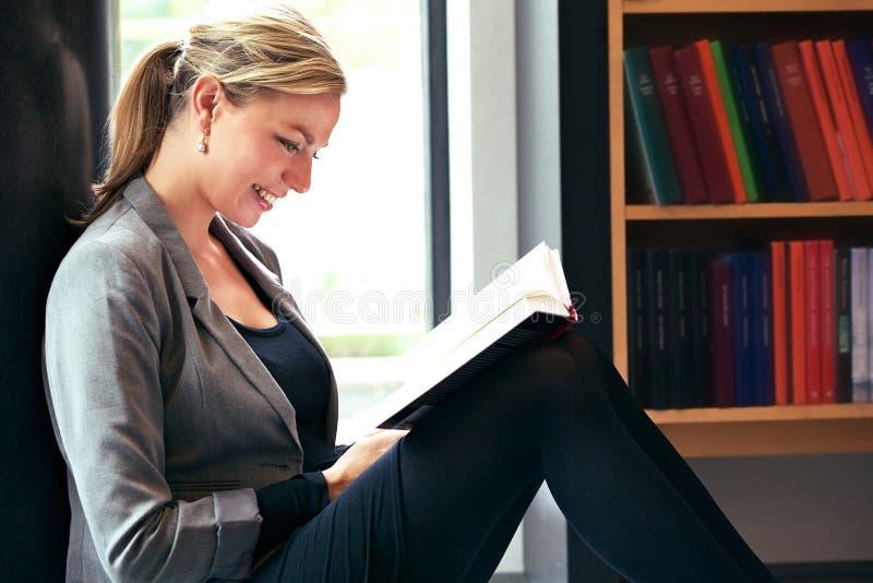 Όμορφη ανάγνωση γυναικών στη βιβλιοθήκη στοκ φωτογραφία με δικαίωμα ελεύθερης χρήσης