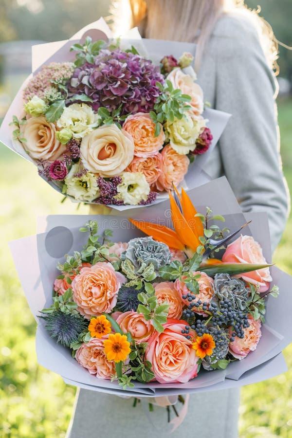 Όμορφη ανθοδέσμη άνοιξη δύο Νέο κορίτσι που κρατά τις ρυθμίσεις λουλουδιών με την ποικιλία των χρωμάτων Βιολέτα, μπλε και ροδάκιν στοκ εικόνες