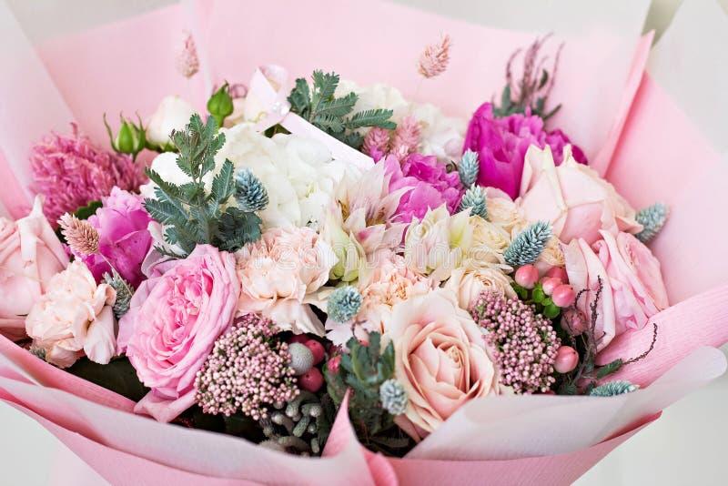 Όμορφη ανθοδέσμη στο ρόδινο τυλίγοντας έγγραφο Τριαντάφυλλα και άλλα λεπτά όμορφα λουλούδια στοκ εικόνα