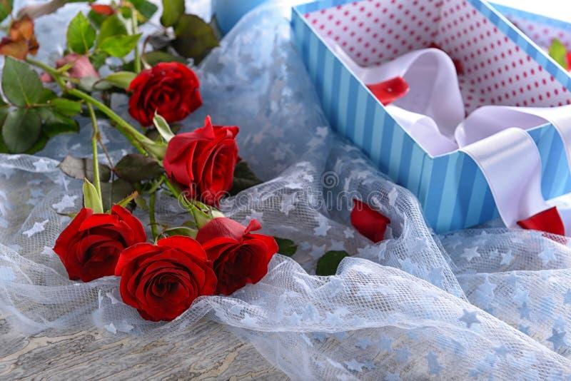 Όμορφη ανθοδέσμη των κόκκινων τριαντάφυλλων και του κιβωτίου δώρων στον πίνακα στοκ εικόνες