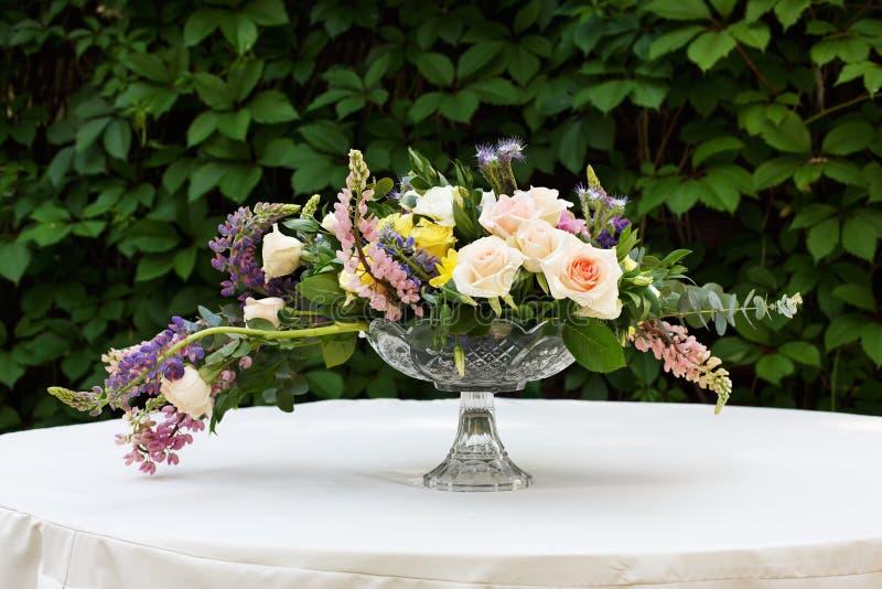 Όμορφη ανθοδέσμη λουλουδιών υπαίθρια Γαμήλια floristic διακόσμηση στον άσπρο πίνακα στοκ φωτογραφία