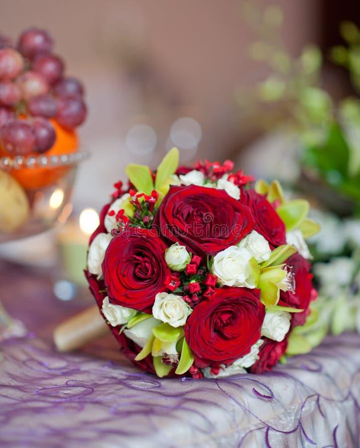 Όμορφη ανθοδέσμη των ροδαλών λουλουδιών στον πίνακα. Γαμήλια ανθοδέσμη των κόκκινων τριαντάφυλλων. Κομψή γαμήλια ανθοδέσμη στον πί στοκ εικόνες με δικαίωμα ελεύθερης χρήσης