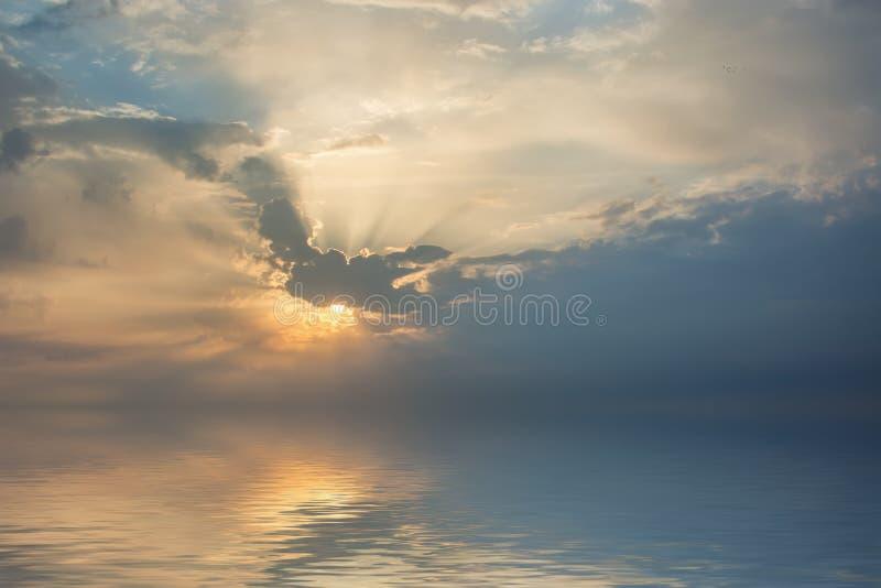 Όμορφη αντανάκλαση στο νερό του ήλιου πίσω από τα σύννεφα στοκ φωτογραφία