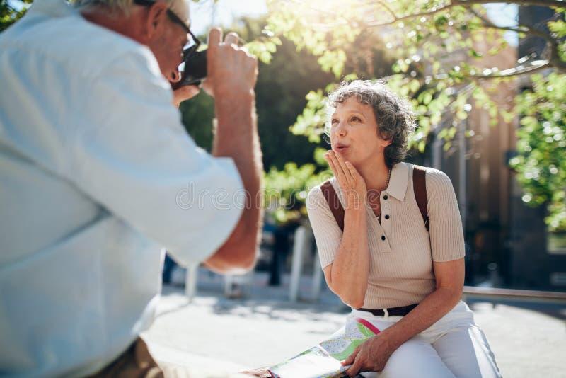 Όμορφη ανώτερη γυναίκα που φυσά ένα φιλί στη κάμερα στοκ εικόνα με δικαίωμα ελεύθερης χρήσης