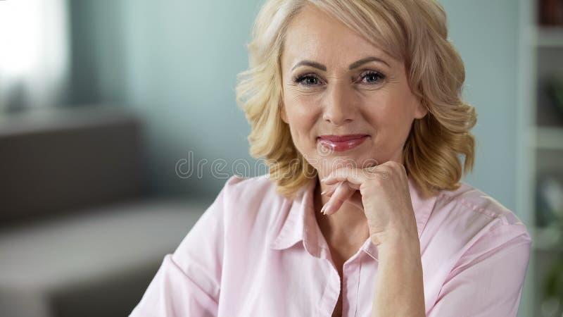 Όμορφη ανώτερη κυρία που εξετάζει τη κάμερα, χαμόγελο στο πρόσωπο, ευτυχής υγιής γυναίκα στοκ εικόνα