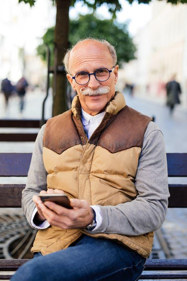 όμορφη απόλαυση ημέρας Εύθυμη ώριμη συνεδρίαση ατόμων στον ξύλινο πάγκο με το τηλέφωνο που δακτυλογραφεί και που χαμογελά στοκ εικόνες