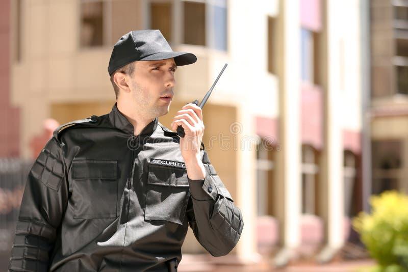 Όμορφη αρσενική φρουρά ασφάλειας που χρησιμοποιεί τη φορητή ραδιο συσκευή αποστολής σημάτων υπαίθρια στοκ φωτογραφία