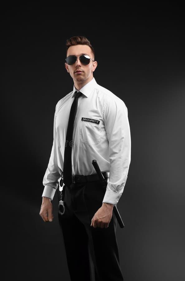 Όμορφη αρσενική φρουρά ασφάλειας σε ομοιόμορφο στο σκοτεινό υπόβαθρο στοκ φωτογραφία με δικαίωμα ελεύθερης χρήσης