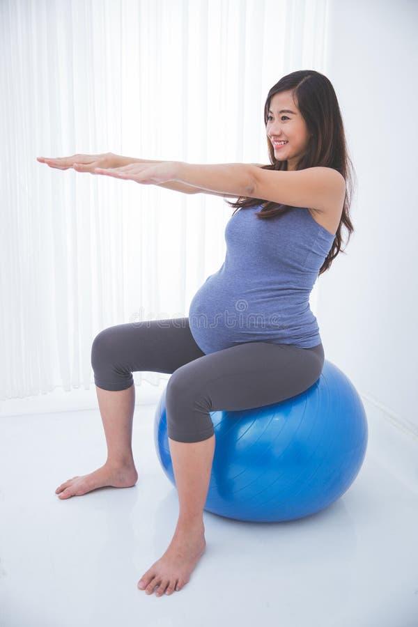 Όμορφη ασιατική έγκυος γυναίκα που κάνει την άσκηση με μια ελβετική σφαίρα, στοκ εικόνες με δικαίωμα ελεύθερης χρήσης