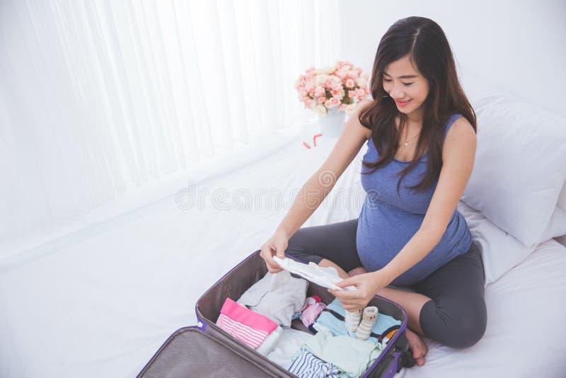 Όμορφη ασιατική έγκυος γυναίκα που οργανώνει τα ενδύματα μωρών σε ένα κοστούμι στοκ φωτογραφία με δικαίωμα ελεύθερης χρήσης