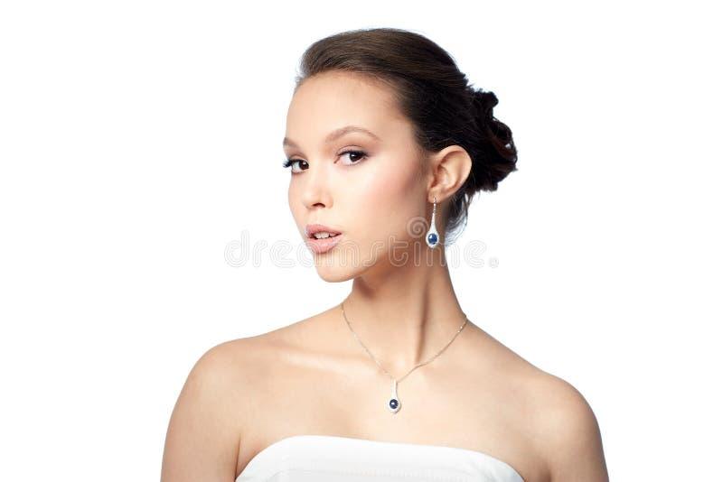 Όμορφη ασιατική γυναίκα με το σκουλαρίκι και το κρεμαστό κόσμημα στοκ εικόνα