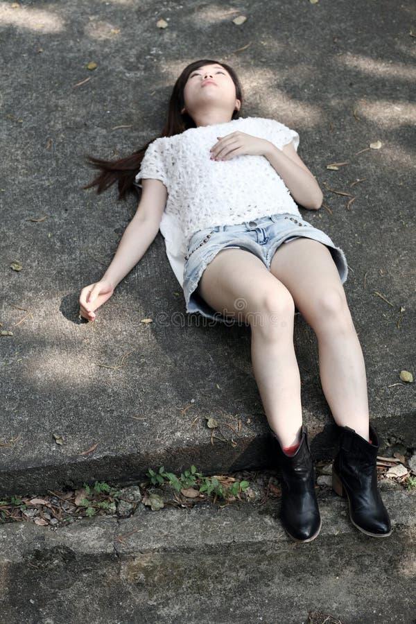 Όμορφη ασιατική γυναίκα που βρίσκεται στο πάτωμα τσιμέντου στοκ εικόνες