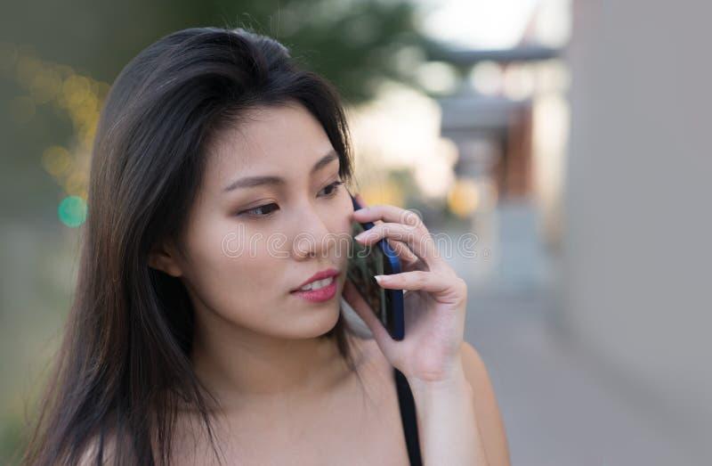 Όμορφη ασιατική γυναίκα που ελέγχει τα μηνύματά της στοκ εικόνες