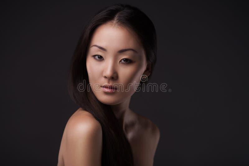 Όμορφη ασιατική γυναίκα που εξετάζει τη κάμερα στοκ φωτογραφία