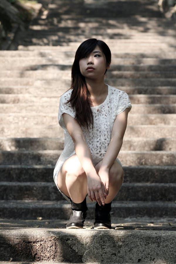 Όμορφη ασιατική γυναίκα που κάθεται οκλαδόν στα βήματα τσιμέντου στοκ εικόνες