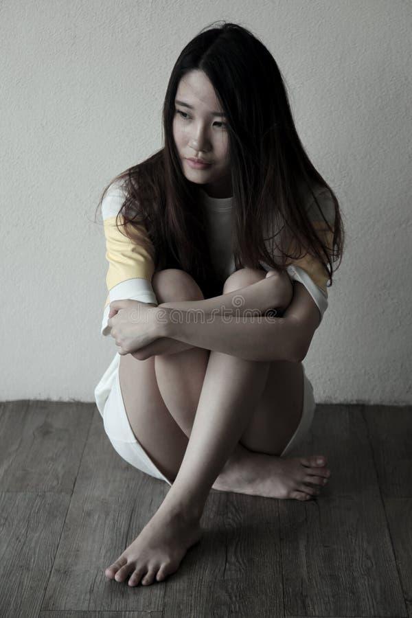 Όμορφη ασιατική γυναίκα που κοιτάζει στην πλευρά που αισθάνεται λυπημένη στοκ φωτογραφία