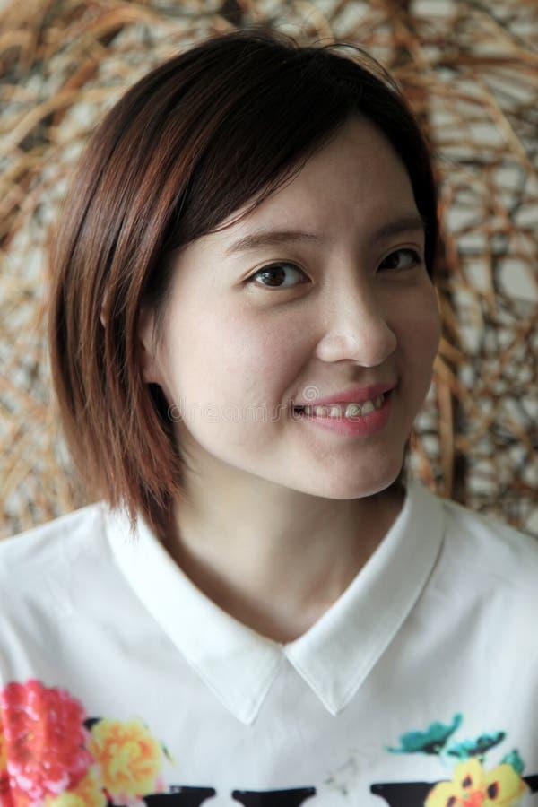 Όμορφη ασιατική γυναίκα που χαμογελά γλυκά να εξετάσει το θεατή στοκ φωτογραφία με δικαίωμα ελεύθερης χρήσης