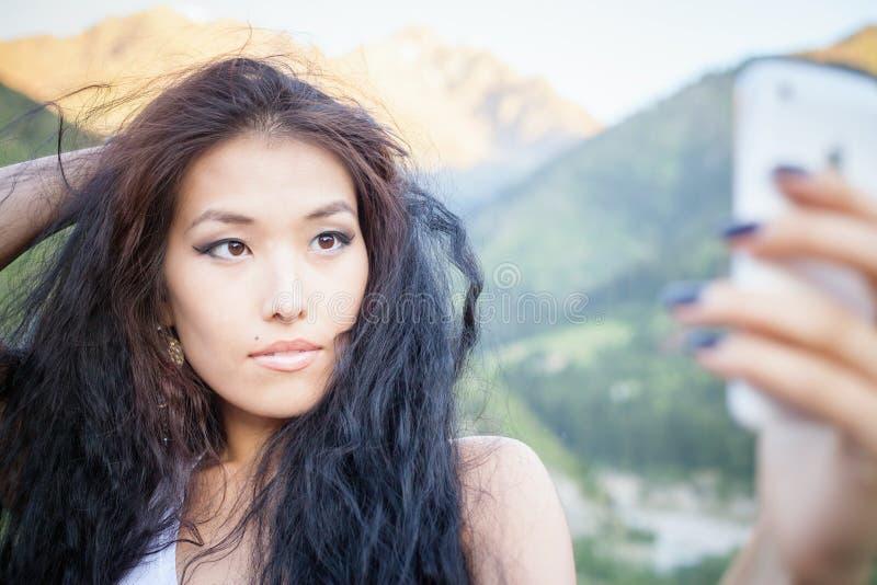 Όμορφη ασιατική γυναίκα που χαμογελά στο τοπίο βουνών στοκ εικόνα
