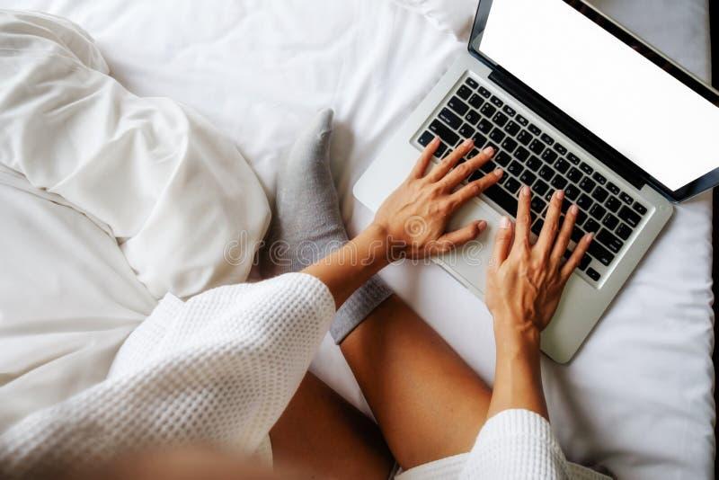 Όμορφη ασιατική γυναίκα που χρησιμοποιεί τον υπολογιστή με το φως πρωινού στοκ εικόνα