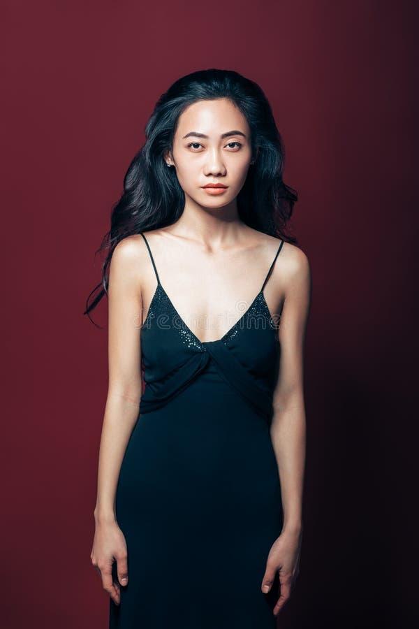 Όμορφη ασιατική γυναίκα στη μαύρη τοποθέτηση φορεμάτων στο στούντιο στοκ εικόνα με δικαίωμα ελεύθερης χρήσης