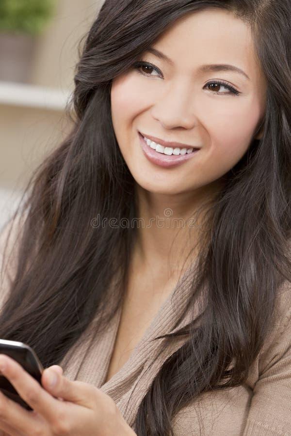 Όμορφη ασιατική κινεζική γυναίκα που χρησιμοποιεί το έξυπνο τηλέφωνο στοκ εικόνα με δικαίωμα ελεύθερης χρήσης
