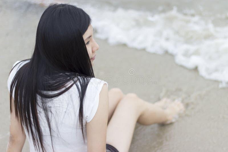 Όμορφη ασιατική πρότυπη συνεδρίαση στην παραλία στοκ εικόνα