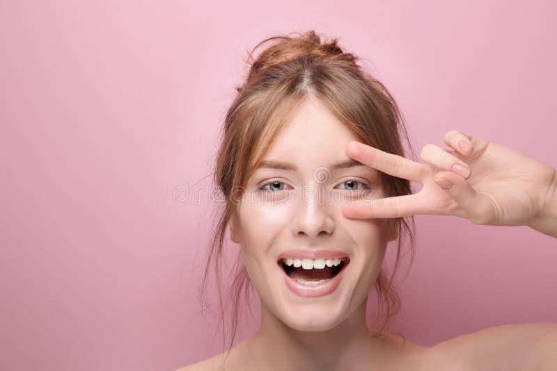 Όμορφη αστεία νέα γυναίκα με το μεταξωτό δέρμα στο υπόβαθρο χρώματος στοκ εικόνες με δικαίωμα ελεύθερης χρήσης