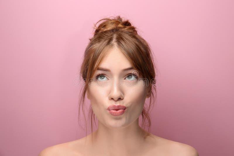 Όμορφη αστεία νέα γυναίκα με το μεταξωτό δέρμα στο υπόβαθρο χρώματος στοκ φωτογραφία με δικαίωμα ελεύθερης χρήσης