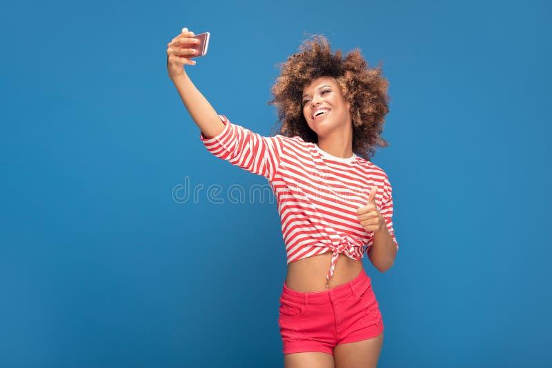 Όμορφη αφρικανική γυναίκα που κρατά το κινητό τηλέφωνο και το χαμόγελο στοκ φωτογραφίες με δικαίωμα ελεύθερης χρήσης