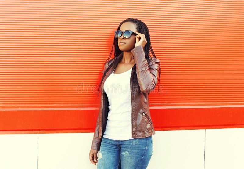 Όμορφη αφρικανική γυναίκα που φορά ένα σακάκι και τα γυαλιά ηλίου δέρματος στοκ φωτογραφία