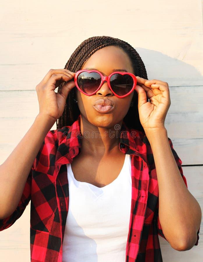 Όμορφη αφρικανική γυναίκα στα κόκκινα γυαλιά ηλίου που έχουν τη διασκέδαση στοκ εικόνες