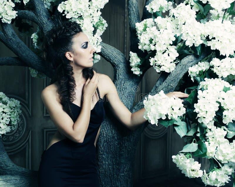 Όμορφη βασίλισσα στη μαύρη τοποθέτηση φορεμάτων κοντά στο δέντρο στοκ φωτογραφία με δικαίωμα ελεύθερης χρήσης