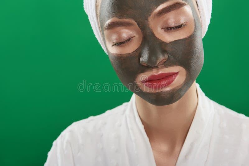 Όμορφη γαλήνια κυρία με τις ιδιαίτερες προσοχές που χρησιμοποιούν την του προσώπου μάσκα αργίλου στοκ φωτογραφίες