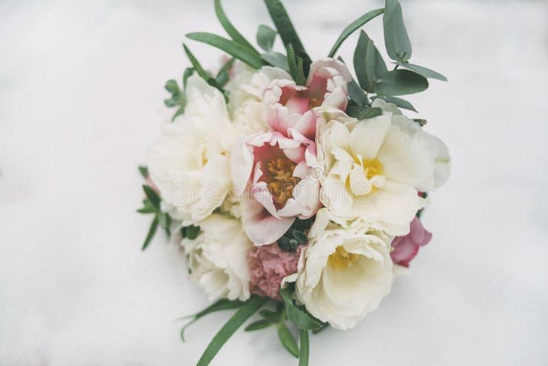 Όμορφη γαμήλια ανθοδέσμη νυφών ` s στο χιόνι στοκ φωτογραφία