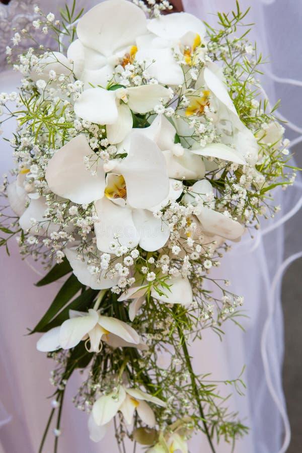Όμορφη γαμήλια ανθοδέσμη των άσπρων ορχιδεών στα χέρια της νύφης στοκ φωτογραφίες