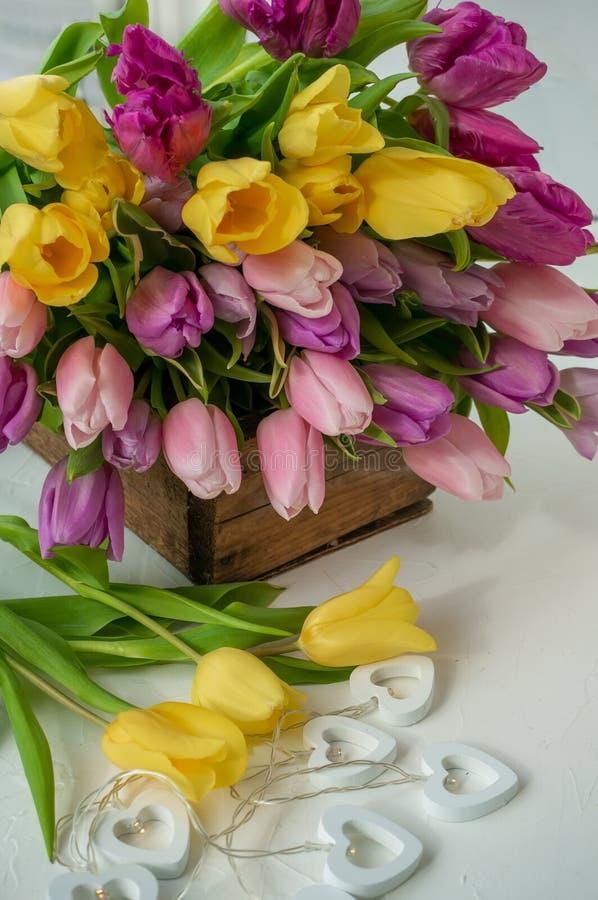 Όμορφη γιρλάντα των άσπρων καρδιών σε ένα υπόβαθρο των ρόδινων τουλιπών Συγχαρητήρια r στοκ φωτογραφία με δικαίωμα ελεύθερης χρήσης