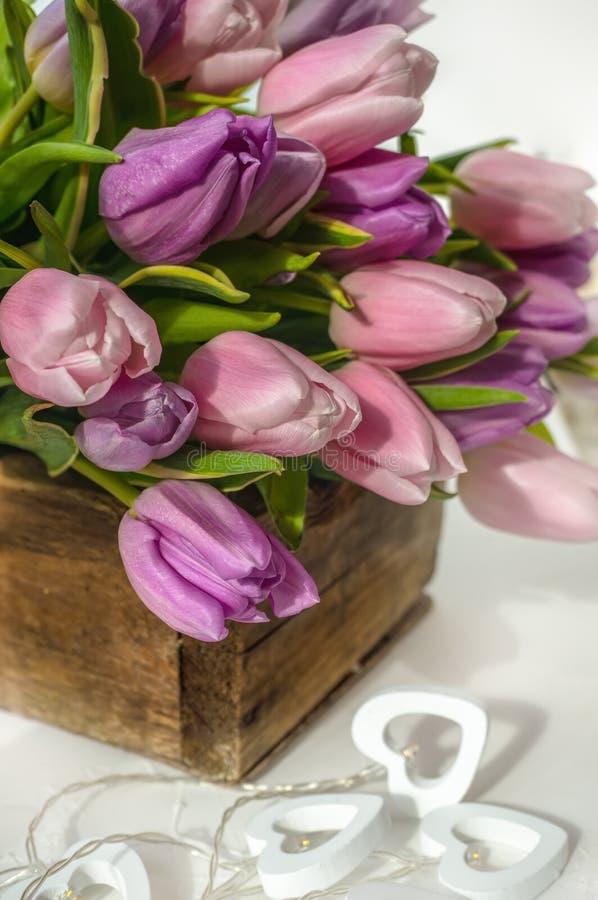 Όμορφη γιρλάντα των άσπρων καρδιών σε ένα υπόβαθρο των ρόδινων τουλιπών Συγχαρητήρια στοκ φωτογραφίες