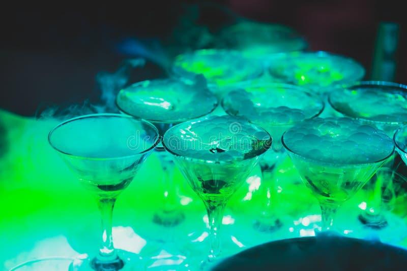 Όμορφη γραμμή πυραμίδων διαφορετικών χρωματισμένων κοκτέιλ οινοπνεύματος με τη μέντα στη γιορτή Χριστουγέννων, το tequila, martin στοκ εικόνα με δικαίωμα ελεύθερης χρήσης