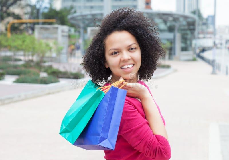 Όμορφη γυναίκα αφροαμερικάνων με τις τσάντες αγορών στοκ φωτογραφία με δικαίωμα ελεύθερης χρήσης
