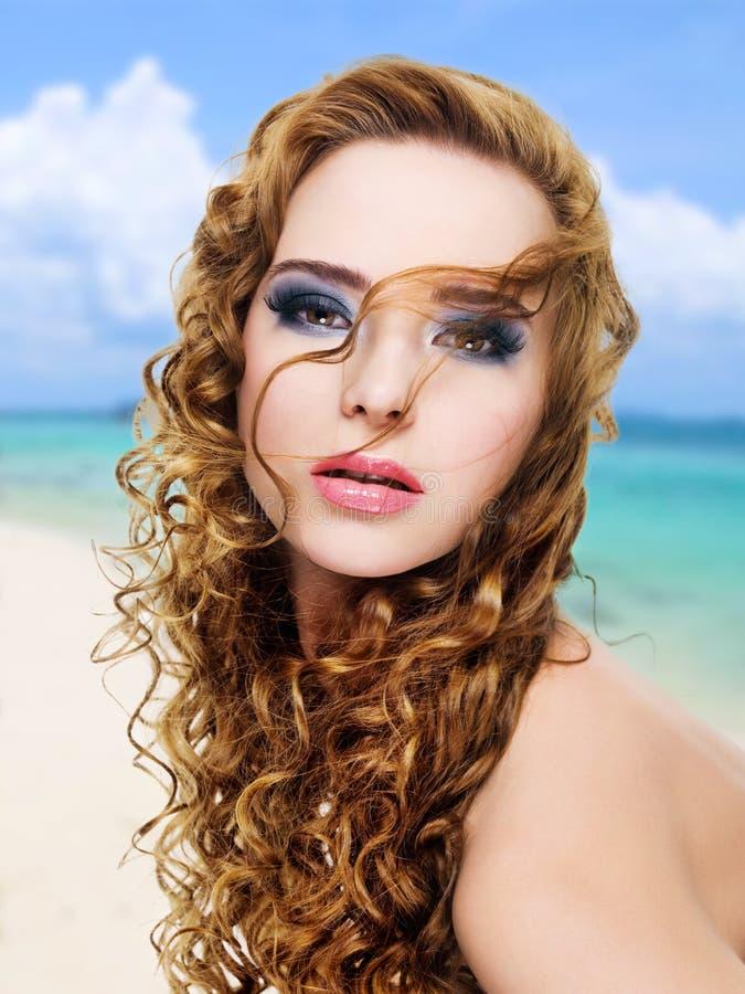 Όμορφη γυναίκα γοητείας με τα μακριά σγουρά τριχώματα στοκ φωτογραφία