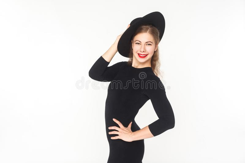 Όμορφη γυναίκα ευτυχίας στο καπέλο, μαύρη γενική τοποθέτηση στη κάμερα στοκ εικόνα με δικαίωμα ελεύθερης χρήσης